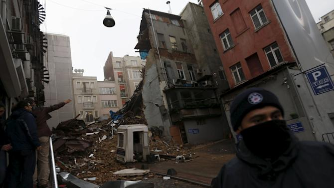 A riot policeman stands guard near collapsed buildings in Istanbul, Turkey