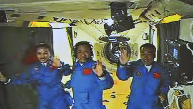 In this image made off the screen at the Beijing Aerospace Control Center and released by China's Xinhua News Agency, Chinese astronauts, from left, Wang Yaping, Zhang Xiaoguang and Nie Haisheng, wave inside the Tiangong-1 space module Thursday, June 13, 2013. China's Shenzhou-10 manned spacecraft successfully completed an automated docking with the orbiting space module Thursday and the three astronauts climbed aboard what will be their home for the next week, state media reported. (AP Photo/Xinhua) NO SALES