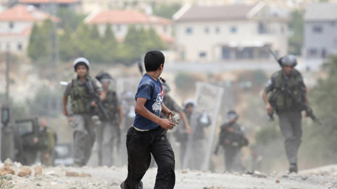 A Palestinian youth carries stones as he runs away from Israeli troops during clashes with Israeli troops during the weekly protest against the expansion of the nearby Jewish settlement of Kdumim, in the northern West Bank village of Kufr Qaddum, Friday, June 22, 2012. (AP Photo/Nasser Ishtayeh)