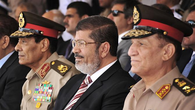 In this image released by the Egyptian President, Egyptian Field Marshal Gen. Hussein Tantawi, left, and new President Mohammed Morsi, center, attend a medal ceremony, at a military base east of Cairo, Egypt, Thursday, July 5, 2012. A Palestinian official says Gaza's prime minister will head to Cairo within the next two weeks to meet with Egypt's new Islamist president, who has close ties with the territory's Hamas rulers. (AP Photo/Mohammed Abd El Moaty, Egyptian Presidency)