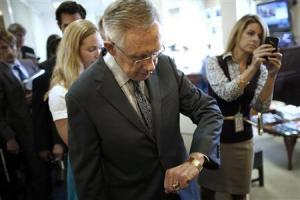 Reid checks his watch after a news conference at the U.S. Capitol in Washington
