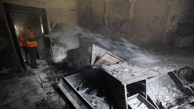 FILE - A Syrian municipality worker extinguishes a burned court room that was set on fire by Syrian anti-government protesters, in the southern city of Daraa, Syria, Monday, March 21, 2011. (AP Photo/Hussein Malla, File)