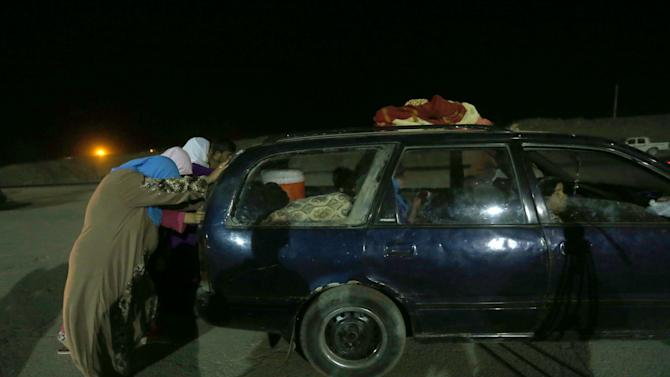 Iraqi women, fleeing from a northern Iraqi town, help push a car after it broke down, as they cross to a secure area, at a Kurdish security forces checkpoint, in the Khazer area between the Iraqi city of Mosul and the Kurdish city of Irbil, northern Iraq, Wednesday June 25, 2014. Sunni insurgents who seized Iraq's second largest city attacked a nearby Christian village on Wednesday, bringing their fight closer to the largely Kurdish regions of northern Iraq which had remained so far largely untouched from the chaos sweeping the country. (AP Photo/Hussein Malla)