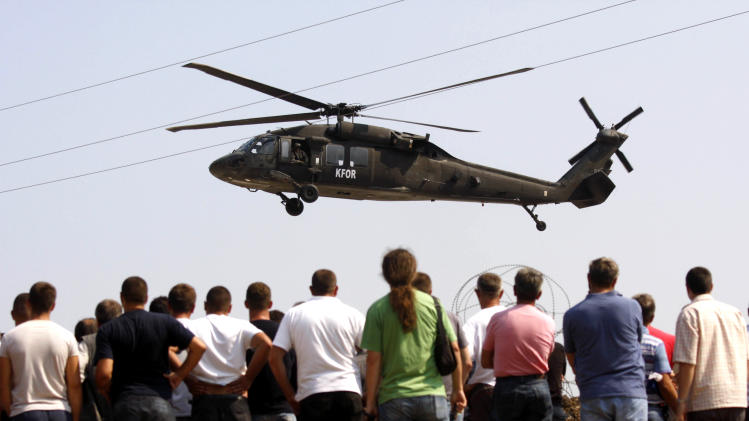 A NATO peacekeeping force helicopter hovers as local Serbs gather at the Jarinje border crossing between Serbia and Kosovo, Friday, Sept. 16, 2011. An EU spokesman in Kosovo says helicopters are being used to ferry staff and supplies to border crossings after minority Serbs blocked main road to the tense areas. (AP Photo/Zveki)