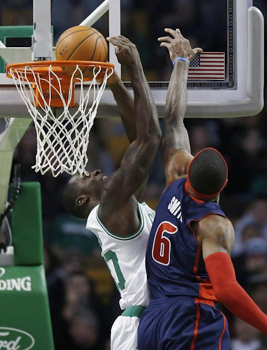 Boston Celtics' Brandon Bass, left, scores in front of Detroit Pistons' Josh Smith (6) in the first quarter of an NBA basketball game in Boston, Sunday, March 9, 2014