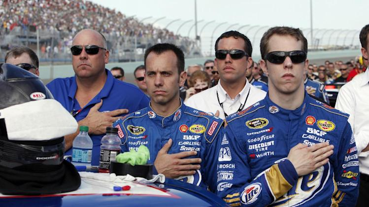 Brad Keselowski and members of his crew listen to the national anthem before the NASCAR Sprint Cup Series auto race at Homestead-Miami Speedway, Sunday, Nov. 18, 2012, in Homestead, Fla. (AP Photo/The Miami Herald, Andrew Uloza)  MAGS OUT