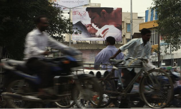 "Indian commuters move past a poster of Bollywood film ""Jism 2""  in Hyderabad, India, Thursday, Aug. 2, 2012. ""Jism 2"" stars a hard-core porn actress, and it does have that pesky title. But it's not a"