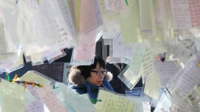 A Catholic prays behind papers, bearing New Year wishes, tied to trees at Myeongdong Catholic Cathedral in Seoul, South Korea, Monday, Dec. 31, 2102. The cathedral is Korea's oldest parish church and the symbol of Korean Catholics. (AP Photo/Ahn Young-joon)