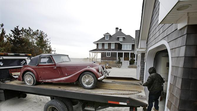 Adrian Agullar removes a ruined vintage automobile from the garage of a storm-damaged beach front home in Mantoloking, N.J., Friday, Feb. 22, 2013. New Jersey has reached another milestone in its recovery 116 days after Superstorm Sandy struck. One of the hardest-hit Jersey shore communities, Mantoloking, will allow its residents to begin moving back home Friday. It is the last shore town to do so. (AP Photo/Mel Evans)