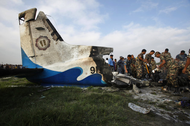Nepalese police search through the debris at the crash site of a Sita Air airplane near Katmandu, Nepal, early Friday, Sept. 28, 2012.  The plane carrying trekkers into the Everest region crashed just