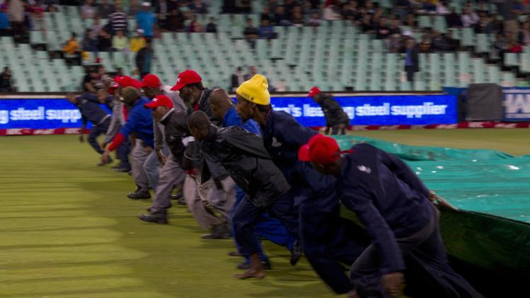 Ground staff move the covers after rain delayed play in the cricket T20 International cricket match between Australia and South Africa in Durban