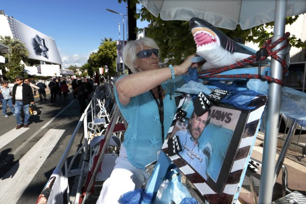 Cinema fan Santoro adjusts a model of a shark as featured in the movie Jaws at the 66th Cannes Film Festival