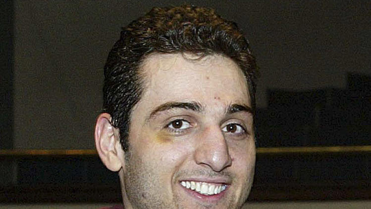 FILE - In this Feb. 17, 2010, photo, Tamerlan Tsarnaev smiles after accepting the trophy for winning the 2010 New England Golden Gloves Championship in Lowell, Mass. Tsarnaev, the Boston Marathon bombing suspect killed in a police shootout, was buried in an undisclosed location outside the city of Worcester, police said Thursday, May 9, 2013.  (AP Photo/The Lowell Sun, Julia Malakie, File) MANDATORY CREDIT