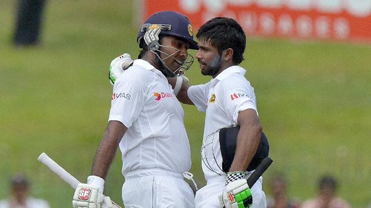 Sri Lankan batsman Niroshan Dickwella (R) is congratulated by teammate Mahela Jayawardene in Colombo on July 25, 2014
