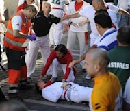 <p>A man receives medical treatment after being injured during the running of the bulls in Pamplona, Spain on July 12, 2012. Six people were hospitalised Thursday after running through the streets with charging bulls at Spain's San Fermin festival, including one visitor from the United States, authorities said.</p>