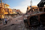 A destroyed Syrian forces tank remains in a damaged street in Atareb in northern Aleppo province on July 2. China joined Russia on Thursday in boycotting a meeting aimed at coordinating efforts to stop the bloodshed in Syria, where three senior army officers were among more than 150 people reported killed in 48 hours