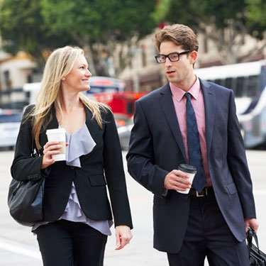 Businesswoman-and-businesswoman-in-street-with-takeaway-coffee_web