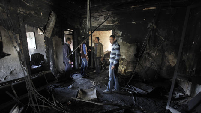 Egyptian workers walk amid the fire damaged headquarters of the Egyptian Soccer Federation two days after protesters set it on fire following a court verdict, in Cairo, Egypt, Monday, March 11, 2013. An Egyptian court on Saturday confirmed the death sentences against 21 people for taking part in a deadly soccer riot but acquitted seven police officials for their alleged role in the violence. Fans enraged by the verdict torched the soccer federation headquarters and a nearby police club in Cairo in protest. (AP Photo/Amr Nabil)
