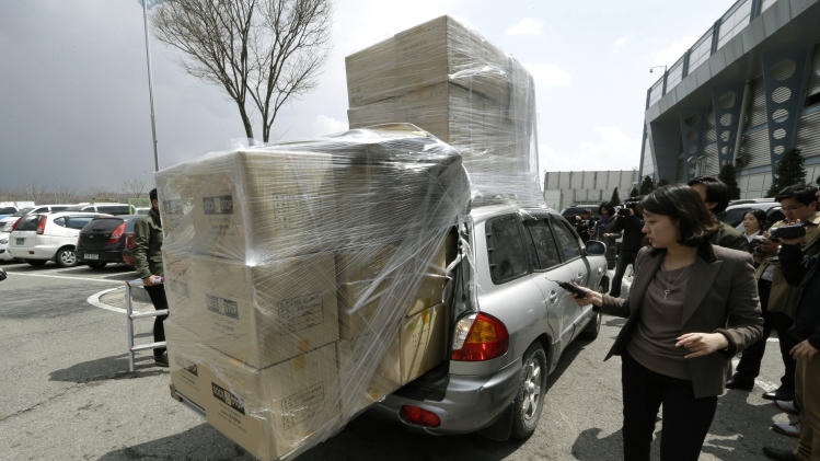 A South Korean vehicle with products from North Korea's Kaesong is surrounded by media upon its arrival at the customs, immigration and quarantine office near the border village of Panmunjom, which has separated the two Koreas since the Korean War, in Paju, north of Seoul, South Korea, Tuesday, April 9, 2013. North Korean workers didn't show up for work at a jointly run factory complex with South Korea on Tuesday, a day after Pyongyang suspended operations at the last remaining major economic link between rivals locked in an increasingly hostile relationship. (AP Photo/Lee Jin-man)
