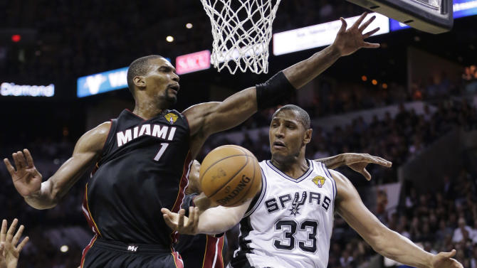 San Antonio Spurs forward Boris Diaw (33) passes around Miami Heat center Chris Bosh (1) during the second half in Game 2 of the NBA basketball finals on Sunday, June 8, 2014, in San Antonio
