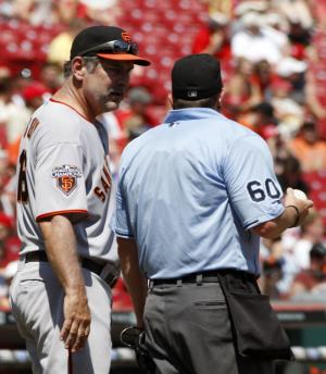 San Francisco Giants manager Bruce Bochy, left , has words with home plate umpire Marty Foster, right, after Cincinnati Reds' Chris Heisey was hit by a pitch in the seventh inning of a baseball game on Sunday, July 31, 2011, in Cincinnati. The Reds won 9-0. (AP Photo/David Kohl)