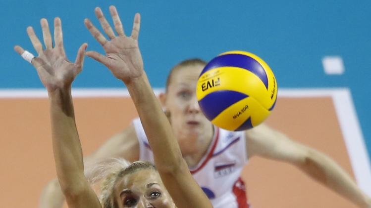 Bavykina of Russia jumps to block the ball spiked by Carvalho of Brazil during their FIVB Women's Volleyball World Grand Prix 2014 final round match in Tokyo