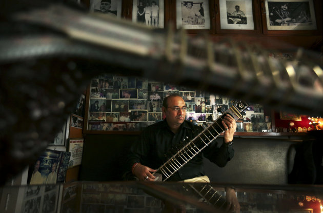 "Indian traditional instrument craftsman Sanjay Sharma plays a sitar at his store Riki Ram's Music in New Delhi, India, Thursday, Dec. 13, 2012. For close to a 100 years Sharma's family has created musical instruments for legendary Indian musicians. But none more famous than sitar virtuoso Ravi Shankar who died Tuesday at age 92. Described as ""the godfather of world music"" by Beatle George Harrison, Shankar introduced millions of Westerners to the sitar and the centuries-old traditions of Indian classical music.(AP Photo/Kevin Frayer)"