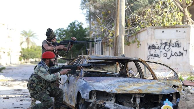 Pro-government Libyan forces, who are backed by locals, aim their weapons during clashes in Benghazi