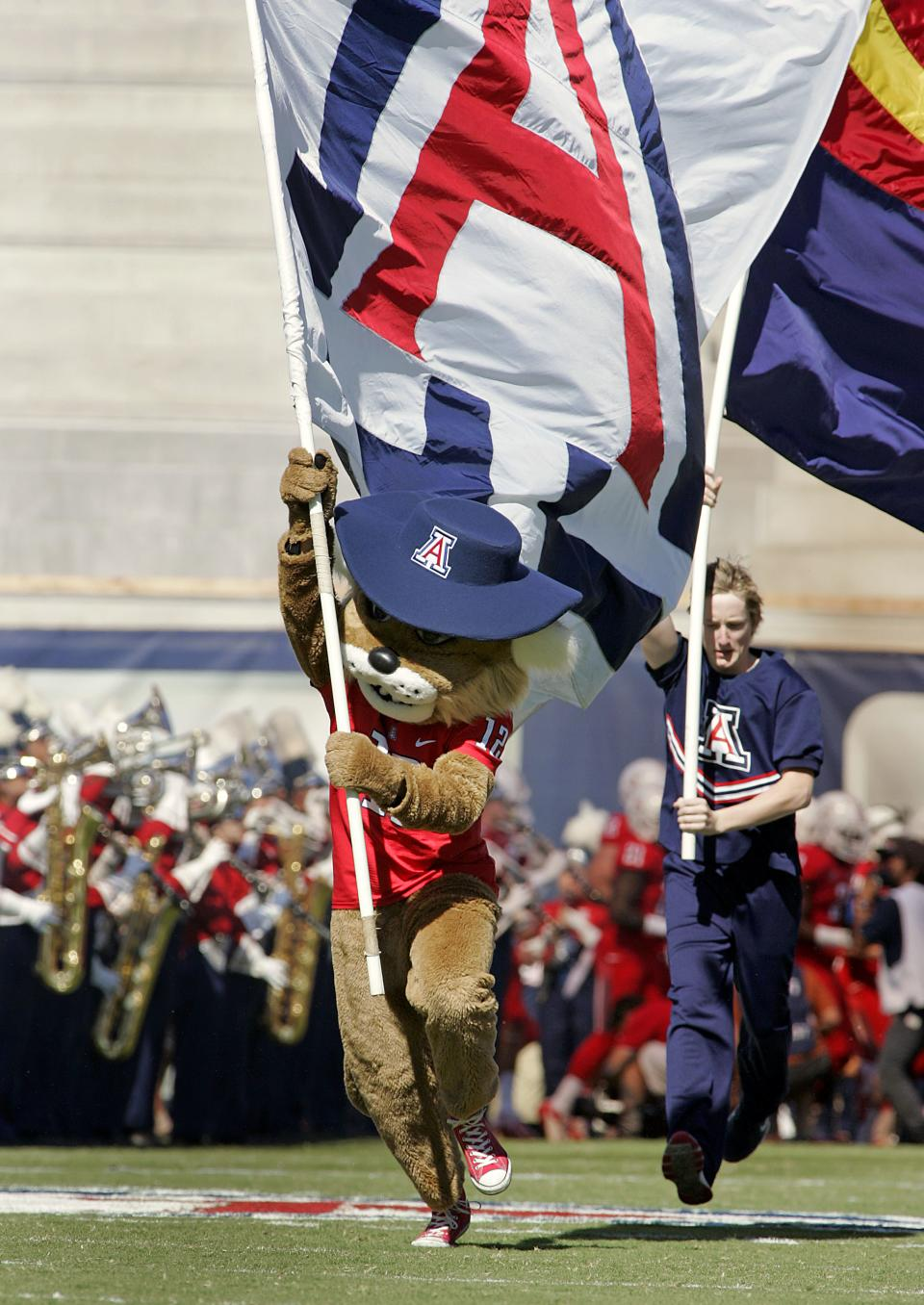 Arizona's mascot Wilbur the Wildcat, center, and a cheerleader carry flags as they run onto the field before the start of an NCAA college football game against Southern California at Arizona Stadium in Tucson, Ariz., Saturday, Oct. 27, 2012. (AP Photo/John Miller)