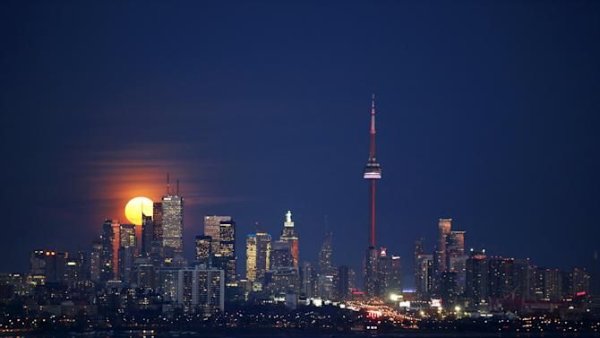 The moon rises behind the skyline and financial district in Toronto