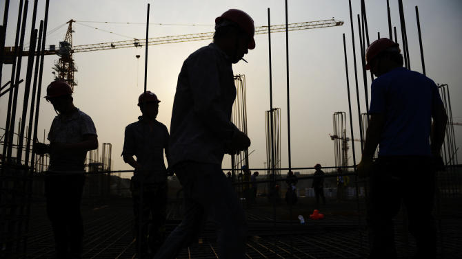 In this Tuesday, May 14, 2013 photo, workers are silhouetted at a construction site of a residential project in Rizhao city in east China's Shandong province. President Xi Jinping and other leaders have pledged to make the economy more productive but have yet to make clear how far they will go in curbing the dominance of state industry and making other changes reform advocates say are required. It is a politically thorny challenge but reform might be driven by slowing growth and concern about tensions due to a lack of new jobs. (AP Photo) CHINA OUT