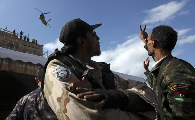 A Libyan military helicopter maneuvers over Tahrir Square as Libyan security forces wave and flash the victory sign during the celebration of the second anniversary of the Libyan revolution in Benghazi, Libya, Sunday, Feb, 17, 2013. Libya&#39;s interim President Mohammed el-Megarif called on Sunday for unity in the North African nation as it celebrates the second anniversary of the uprising that toppled longtime dictator Moammar Gadhafi but plunged the country into lawlessness and economic woes.(AP Photo/Mohammad Hannon)