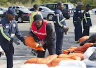 A Department of Public Works employee hands over a sandbag at a distribution center near RFK Stadium in Washington. Across the eastern US, Americans made frantic preparations for a possible superstorm as Hurricane Sandy lumbered north after leaving 59 people dead in the Caribbean