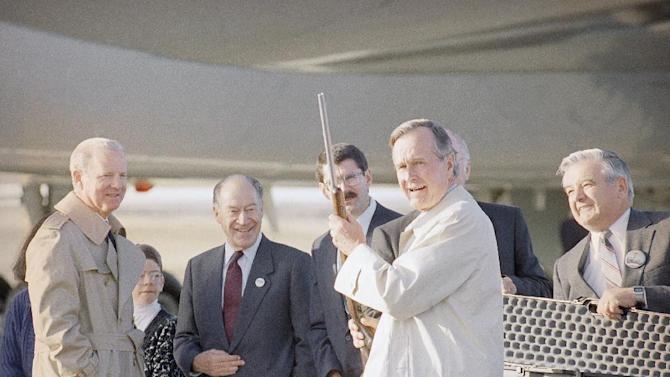 FILE - In this Oct. 25, 1992 file photo, U.S. President George H. Bush displays a rifle given to him as a gift, in Billings, Mont., as his chief of staff James Baker, left, watches during the campaign stop. Bush will continue campaigning at morning on Monday in Montana. (AP Photo/Ron Edmonds, file)