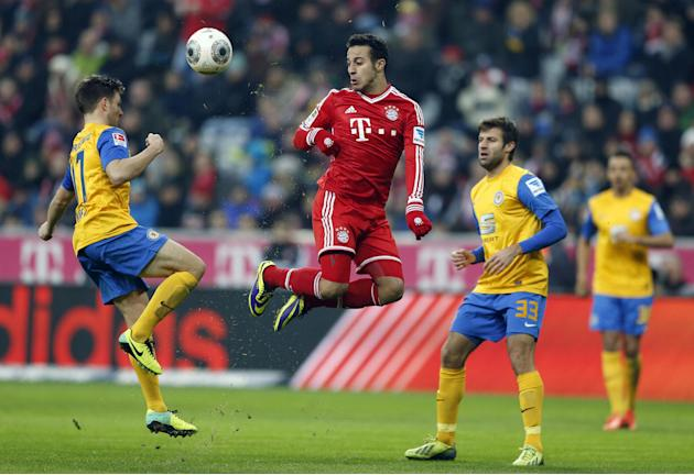 Bayern's Thiago Alcantara of Spain, center, Braunschweig's Kevin Kratz, left, and Braunschweig's Marco Caligiuri challenge for the ball during the German first division Bundesliga soccer match between