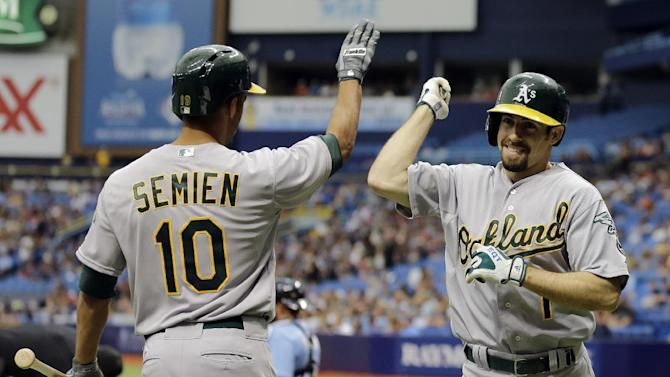 Oakland Athletics' Billy Burns (1) celebrates with Marcus Semien (10) after Burns hit a home run off Tampa Bay Rays pitcher Erasmo Ramirez during the first inning of a baseball game Sunday, May 24, 2015, in St. Petersburg, Fla.  (AP Photo/Chris O'Meara)