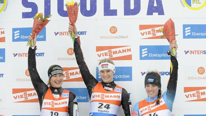 From left, Germany's Anke Wischnewski, second place, Germany's Natalie Geisenberger, first place, USA's Erin Hamlin, third place, celebrate on the podium after their women's race at the Luge World Cup event in Sigulda, Latvia, Sunday, Feb. 19, 2012. (AP Photo/Roman Koksarov)