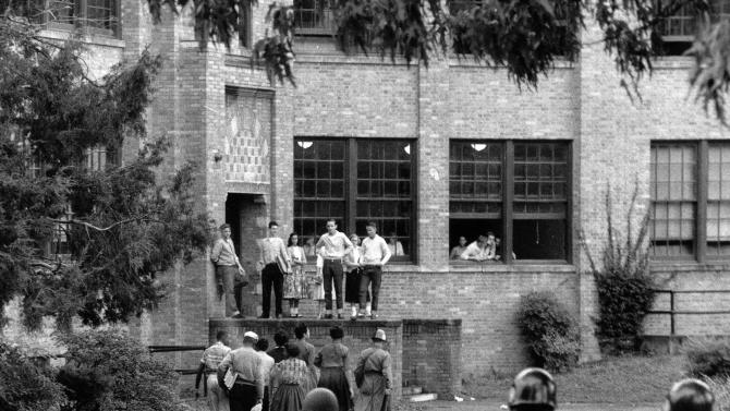 FILE - In this Oct. 15, 1957, file photo, seven of nine black students walk onto the campus of Central High School in Little Rock, Ark., with a National Guard officer as an escort and other troops watch. After decades of court battles and $1 billion of government aid, one the nation's most historic school desegregation efforts may finally be nearing an end. A federal judge on Friday, Nov. 22, 2013, gave preliminary approval to a settlement in a Little Rock desegregation lawsuit that would phase out special court-ordered payments during the 2017-2018 school year. The end, perhaps coincidentally, would come 60 years after the eyes of the nation were first riveted on Little Rock, when President Dwight Eisenhower in 1957 ordered federal troops to ensure safe passage for nine black students walking through angry crowds into the doors of the predominantly white Little Rock Central High School. (AP Photo, Fred Kaufman, File)
