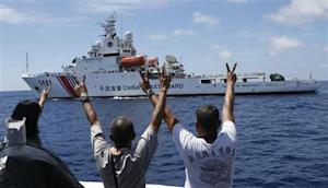 Philippine Marines and a local television reporter gesture towards a Chinese Coast Guard vessel at disputed Second Thomas Shoal in South China Sea