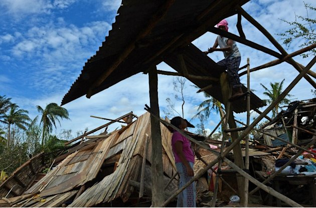 A couple fix their destroyed house in Monte Vista town, Compostela Valley province on December 5, 2012, a day after Typhoon Bopha hit the province.
