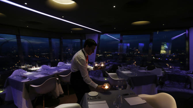 In this picture taken March 6, 2013, a waiter sets a candle on a table in a restaurant at the Zizkov television tower in Prague, Czech Republic. Following its completion in 1992, the 216-meter (236-yard) tall television tower in the Czech capital has become a dominant landmark of the city skyline that offers a breathtaking view of Prague from its restaurant and observation desk. (AP Photo/Petr David Josek)