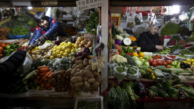FILE - In this Jan. 11, 2013 file photo, a vegetable vendor, left, collects money from a customer at a market in Beijing, China. China's inflation declined in March, 2013, easing pressure on consumers but fueling questions about the strength of its recovery. Government data Tuesday, April 9, 2013 showed consumer prices rose 2.1 percent, down from the previous month's 3.2 percent and well below the official target for the year. Wholesale prices declined by 1.9 percent compared with last year. (AP Photo/Ng Han Guan, File)