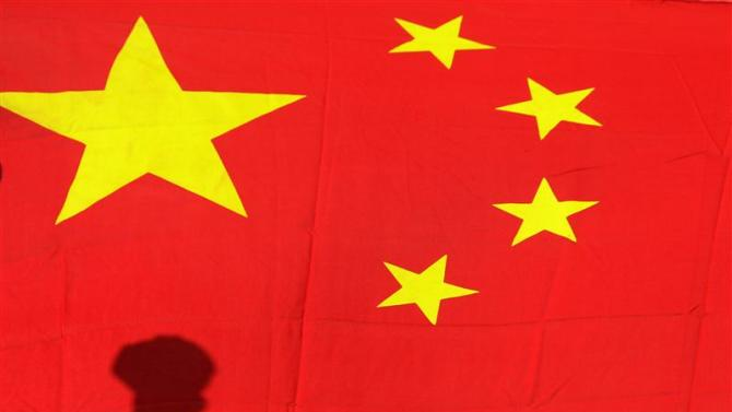 File photo of shadow of clenched fist of protester seen on Chinese national flag during anti-Japan protest in Beijing