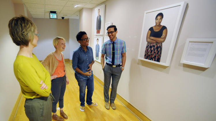 In this photo taken on Monday, April 21, 2014, photographer Carolyn Sherer, left, looks at her new exhibit featuring images of young people with varied sexual identities and preferences during the installation work in Birmingham, Ala. From second left, Foster Noone, 17; Lauren Jacobs, 22; and Ali Massoud, 20, are among a dozen young people who posed for the photos in the exhibit, which opens Wednesday, April 23, at the Birmingham Civil Rights Institute. (AP Photo/Jay Reeves)