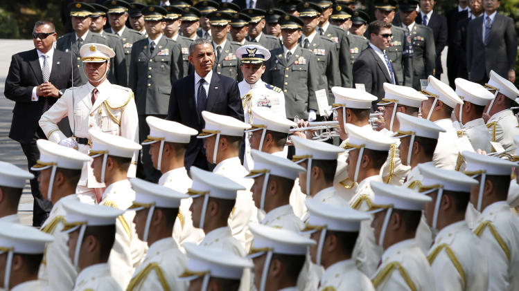 U.S. President Barack Obama, center, inspects an honor guard during a welcoming ceremony at the Imperial Palace in Tokyo Thursday, April 24, 2014. Facing fresh questions about his commitment to Asia, Obama will seek to convince Japan's leaders Thursday that he can deliver on his security and economic pledges, even as the crisis in Ukraine demands U.S. attention and resources elsewhere. (AP Photo/Yuya Shino, Pool)
