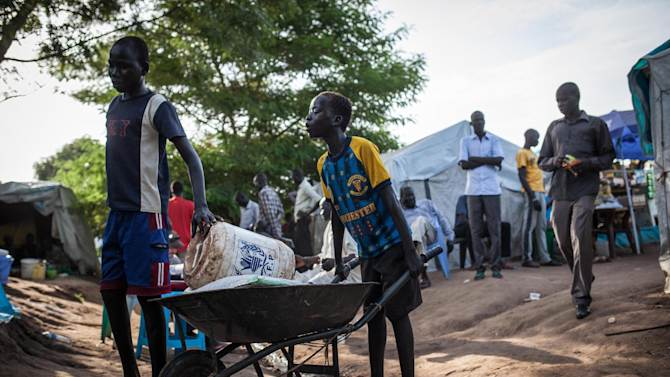 Boys push a wheelbarrow with goods at the Tomping Internally Displaced Persons (IDP) camp in Juba on July 2, 2014