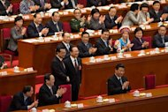 Delegates applaud as China&#39;s outgoing premier Wen Jiabao (C-R) shakes hands with newly elected premier Li Keqiang (C-L) next to President Xi Jinping (lower R) during a session of the National People&#39;s Congress (NPC) at the Great Hall of the People in Beijing on March 15, 2013. China&#39;s parliament installed bureaucrat Li Keqiang as premier in a final step of a landmark power transition