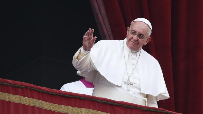 """Pope Francis waves as he delivers a """"Urbi et Orbi"""" (to the city and world) message from the balcony overlooking St. Peter's Square at the Vatican"""