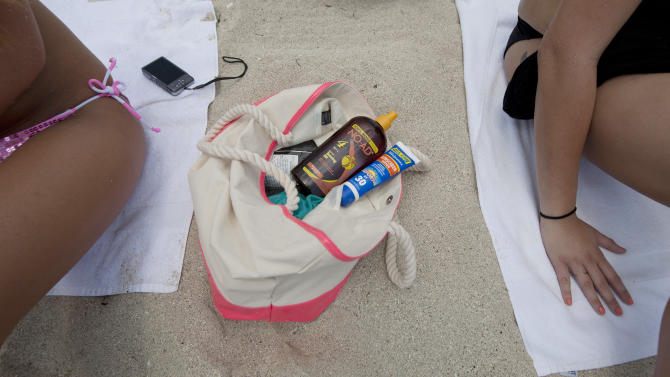"""In this Wednesday, May 9, 2012 photo, Morgan Weese, left, and Brittany Locke carry a supply of sun tanning products in their bag as they sun bathe in Miami Beach, Fla. Weese said she used to """"obsessed"""" with tanning during high school, but now knows the dangers associated with tanning too much - including skin cancer. (AP Photo/J Pat Carter)"""