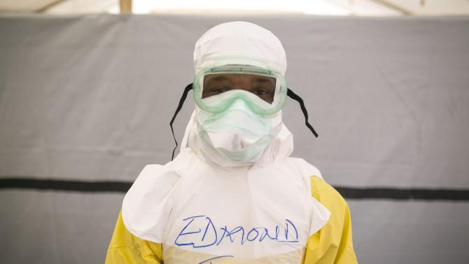 File photo of a health worker putting n protective gear before entering a quarantine zone at a Red Cross facility in the town of Koidu